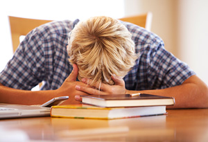 Student Bent Over Books in Library Tired
